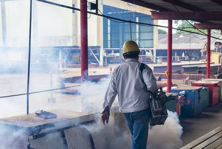 Men are using fogging machine to get rid of mosquitoes and insects in industrial factory.