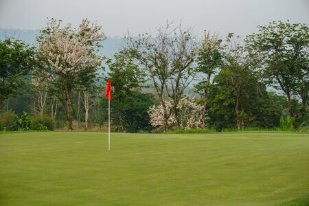Red flag on Green Golf Course and Green Mountain. Imagens