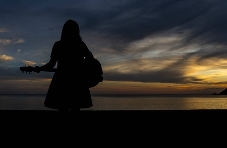 Silhouette of a woman standing playing the guitar at the seaside In the sunset.