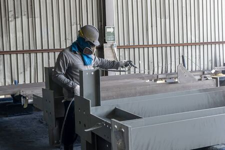 The painter is working to painting the steel structure with spray gun at industrial factory.