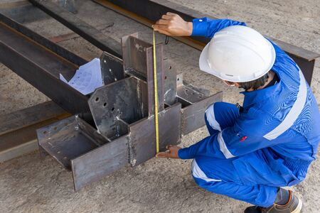 Technicians are using measuring tape to checking the accuracy of the steel structure after assembly before delivery to paint. Stock Photo