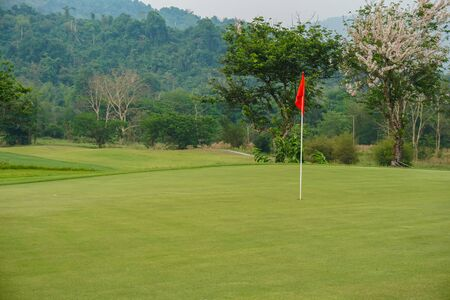 Red flag on Green Golf Course and Green Mountain. 版權商用圖片