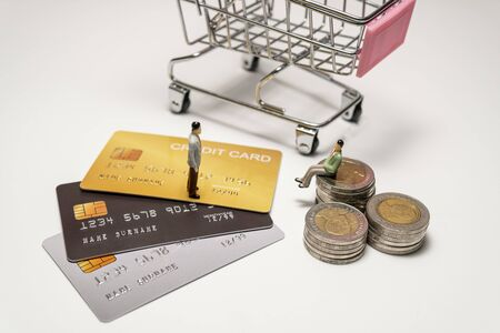 Miniature figure businessman standing on credit card and sitting on stacked coin and cart on back. Concept of spending with credit card or cash. Foto de archivo