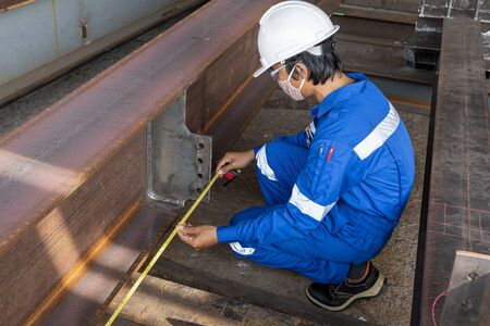 Technicians are using measuring tape to checking the accuracy of the steel structure