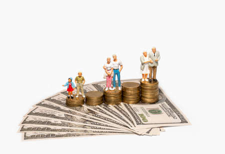 Miniature people couples men and women three ages standing on stacked coin with US dollar bills isolated on white background.