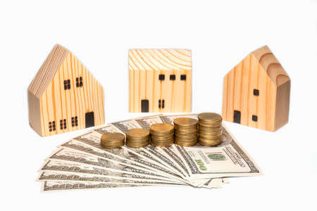 Stacked coin on US dollar bills and three wooden house, isolated on white background. Stockfoto