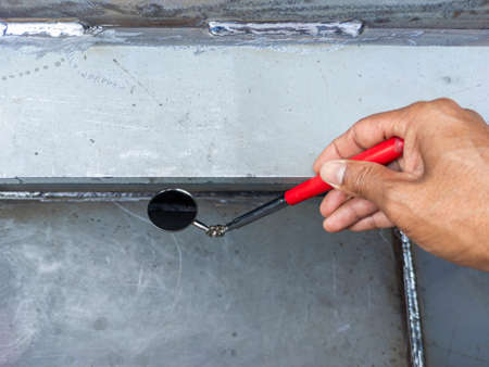 Using welding inspection mirror for check visual welding defects in a niche.