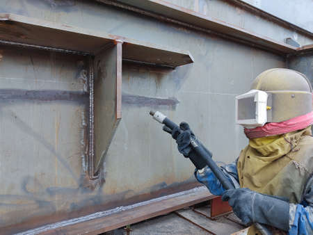 Worker is sandblasting a welding surface and steel structure with pressure blasting pot for create surface profile of steel before painting.
