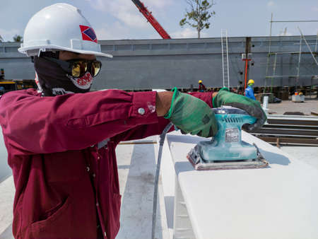Worker is using a Ponceuse Vibrante or Orbital Sander to scrub surface intermediate fire proof paint before painting top coat.