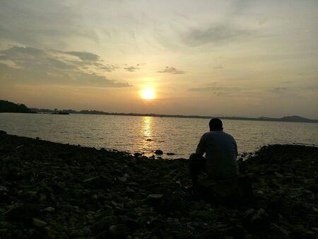man: Man sitting at the beach at sunset.