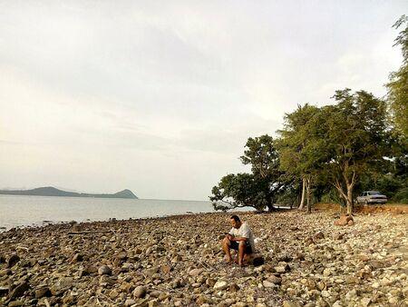 man: Man sitting on stone by sea