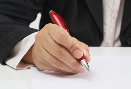 Business woman at her office signing a contract with red pen
