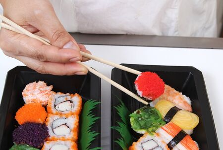 Closeup image of hand and chopstick prepare sushi japanese food photo