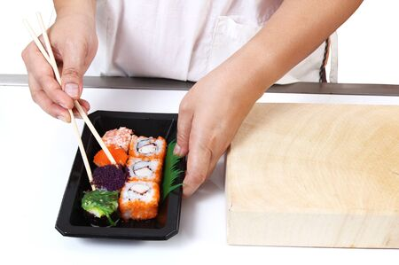 Closeup image of hand and chopstick prepare sushi japanese food