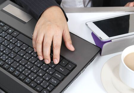 business man working on hes notebook tablet and hot coffee on white table photo