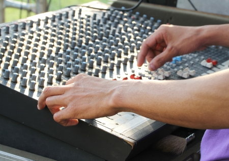 Image of hand of technician doing sound mixing console on sound board photo