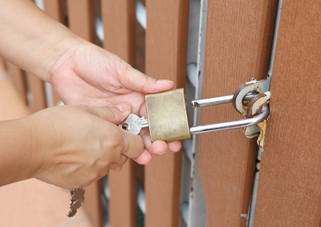 Closeup image of hand use key to open padlock and the brown wooden door  photo