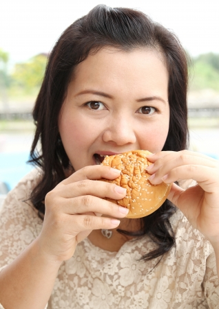 mel: closeup image of asian woman eating hamburger at coffeeshop Stock Photo