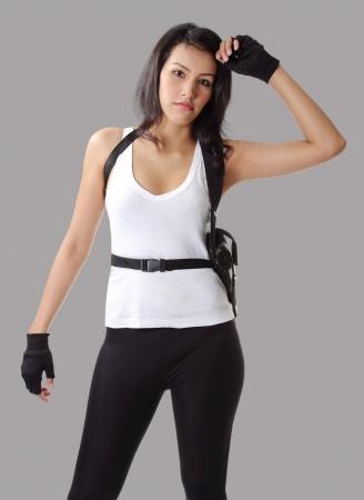 asian woman wearing white vest with her handgun