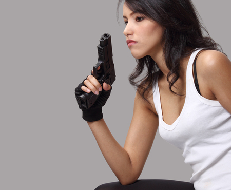 asian woman wearing white vest and holding a gun on her hand  photo