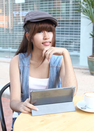 Image of asian student working her job with tablet at coffee shop photo