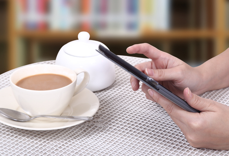 Closeup images of asian woman touch her tablet and hot coffee  photo