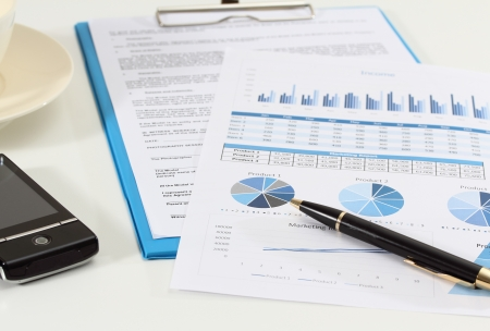 image of graphics and finance report for business with pen mobile phone and coffee Stock Photo