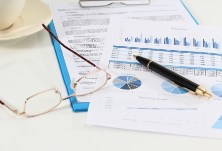 image of graphics and finance report for business with pen and glasses