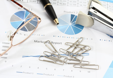 image of graphics and finance report for business with pen glasses paper clips and stapler