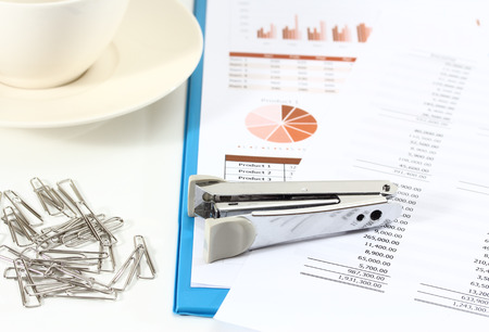 image of graphics and finance report for business with paper clips stapler and coffee
