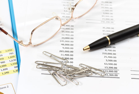 image of graphics and finance report for business with pen glasses and mobile phone