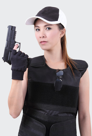 bulletproof: asian woman wearing bulletproof vest and holding a gun on her hand