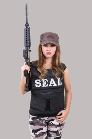 bulletproof vest: asian woman wearing bulletproof vest and holding a rifle on her hand Stock Photo