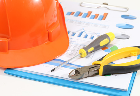 Image of helmet pliers tools and business report for construction on white desk