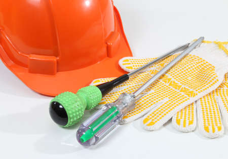 Image of helmet gloves and screwdriver for construction on white desk photo