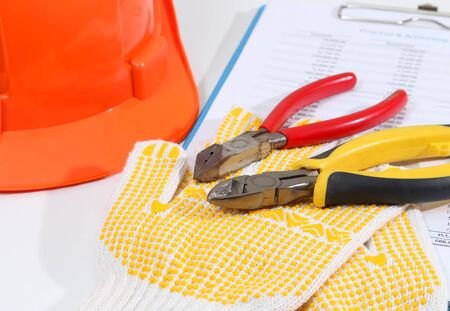 Image of helmet pliers and gloves for construction on white desk Stock Photo
