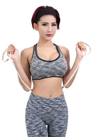 young asian woman in fitness clothes and measuring tape Stock Photo