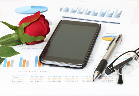 closeup Image of red rose on graph and chart report at the office Stock Photo