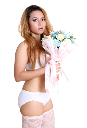 young beautiful asian woman holding flower in sexy bikini and white background