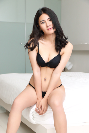 beautiful young asian woman in black bikini at bed room Stock Photo - 99532306