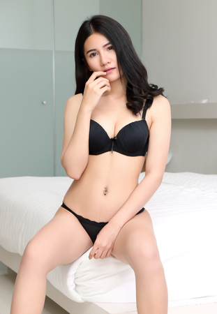 beautiful young asian woman in black bikini at bed room Stock Photo - 99576800