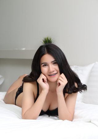beautiful young asian woman in black bikini at bed room Stock Photo - 99576803