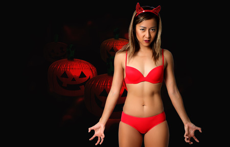 sexy devil woman in red bikini and halloween Archivio Fotografico