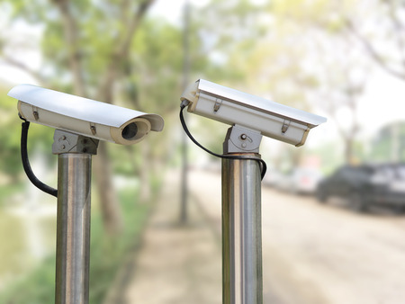 closeup image of CCTV security camera outdoor with blurred background