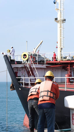 docker: Port worker working with oil barge Editorial