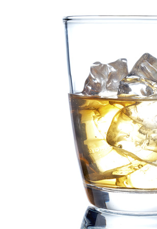 Glass of scotch whiskey and ice on a white background 写真素材