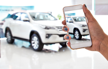 car dealership: using smartphone, car sales Stock Photo