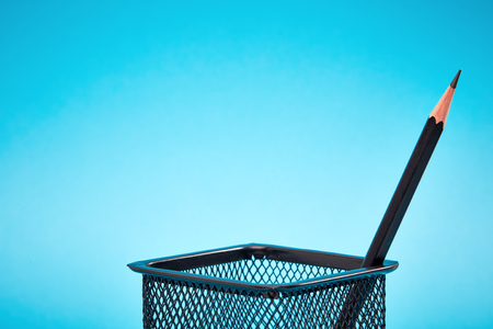 pencil holder: One pencil in a wire mesh pencil holder, Blue background