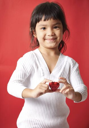 ojos marrones: Beautiful little girl with amazing brown eyes and black hair long holds in his hands Valentine red heart and looks with love and joy in the lens, is cheerful, red background Foto de archivo