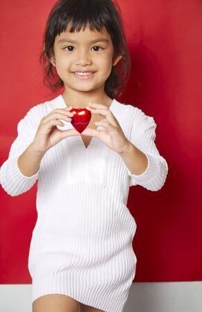 ojos marrones: Ni�a hermosa con ojos marrones y cabello negro sorprendentes mantiene siempre en su coraz�n rojo de San Valent�n manos y mira con amor y alegr�a en la lente, es alegre fondo, rojo